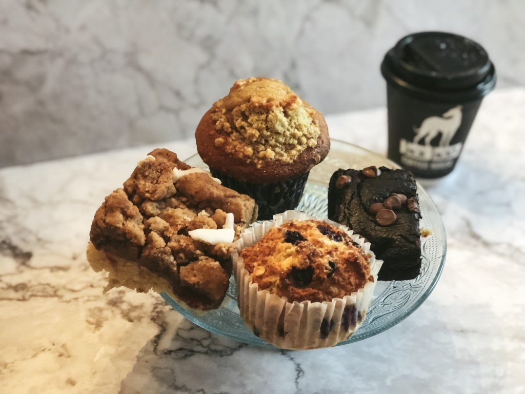 Raspberry crumb cake, apple crumb muffin, vegan brownie, and a blueberry muffin